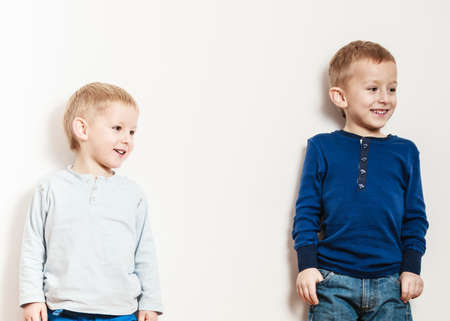 smiled: Free time, fun and independence. Little boys play together indoors. Blonde children wear colorful clothes.