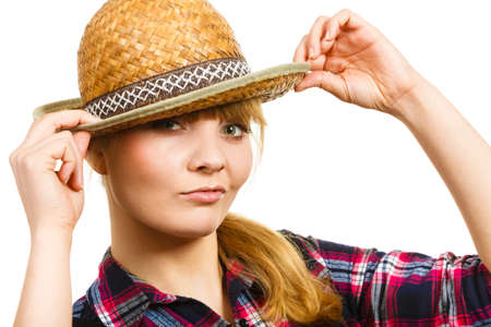 dungarees: Gardening concept. Attractive woman in dungarees, pink check shirt holding sun hat on head. Isolated background