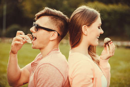 Love and happiness. Young lovely couple eating cupcakes cookies. Smiling people with sweet food spending time in park garden. Stock Photo