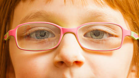 optician: Eyeglasses, vision, eye problems concept. Closeup, face of young toddler girl wearing pink glasses for kids.
