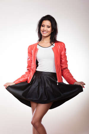 leather skirt: Fashion and style. Beauty gorgeous young mixed race woman wearing stylish red jacket coat and black leather skirt. Fashionable girl posing indoor.