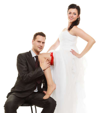 nuptial: Wedding day. Full length happy newly married couple, groom and sexy bride in red garter on leg. Isolated on white background