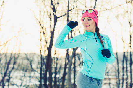 staying fit: Girl jogging in snow park. Staying fit and safe during winter. Nature fitness health safety health concept.