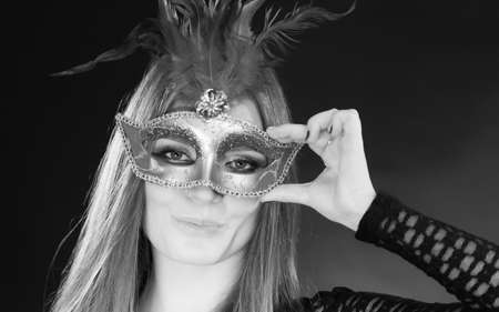 blackwhite: Party time, holidays, people and celebration concept. Woman long hair holding carnival mask close up. Black & white photo