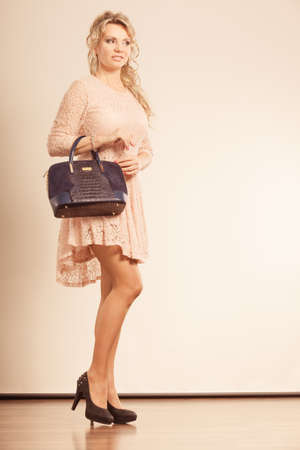 Fashion concept. Beautiful lady with black handbag. Woman is wearing nice high heels and very cute beige dress.