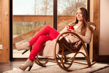 Calm and coziness. Young woman at home sitting comfortable on rocker chair in front of window relaxing in her living room enjoying coffee or tea drink