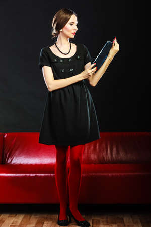 black briefcase: Technology internet business concept. Fashion woman retro style standing with tablet black briefcase in front of red couch
