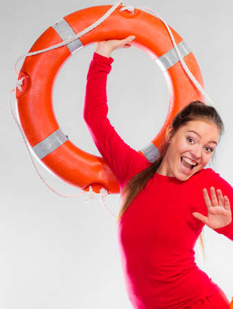 Accident prevention and water rescue. Young woman female smiling lifeguard on duty holding buoy lifesaver equipment having fun on gray Stock Photo
