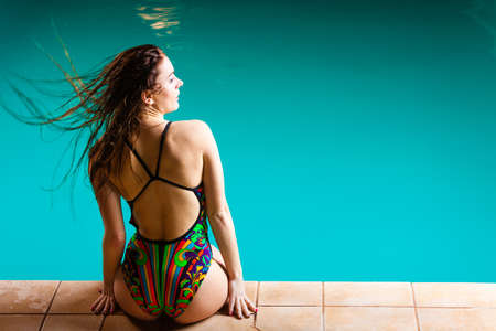 Relax, rest and recreation. Long haired woman back in colorful swimsuit on pool edge. Stock Photo