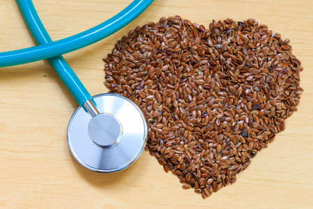 linum: Diet healthcare and checkup concept. Raw flax seeds linseed heart shaped and stethoscope. Healthy food for preventing heart diseases. Stock Photo