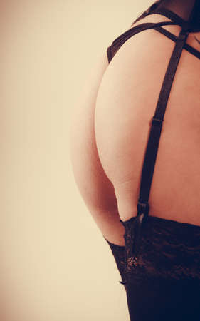 sexiness: Sexiness and beauty of women. Back view of close up ass arse of young attractive girl wearing black sensual lingerie underwear. Stock Photo
