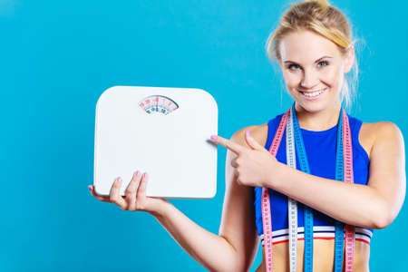 losing control: Healthy lifestyle. Fitness woman with many measure tapes holding weight scale studio shot blue background