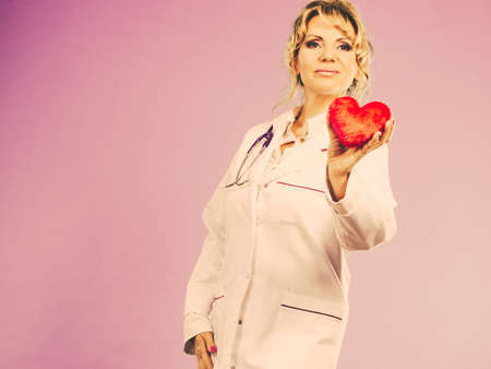 Help people concept. Medical idea of helping. Mature blonde happy doctor cardiologist with red heart enjoy her work. Middle aged woman wearing medic apron. Filtered. Stock Photo