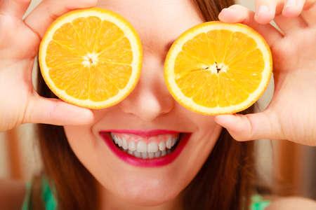 Gelukkig vrouw die ogen met oranje plezier.