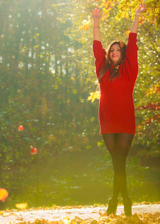 tossing: Girl tossing up leaves. Young woman in autumnal forest playing with foliage. Nature outdoor relax concept.  Stock Photo