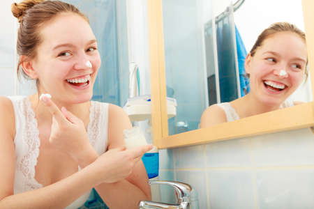 smiled: Happy young woman applying cleansing moisturizing skin cream on face. Girl taking care of dry complexion layering moisturizer. Skincare.