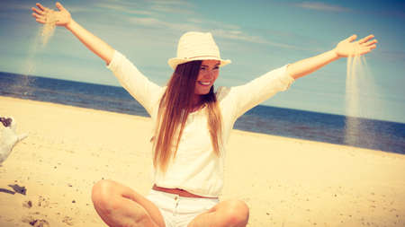 craze: Happiness and craziness. Smiling crazy girl have fun with sand outdoor. Young attractive long haired woman playing on summer beach.