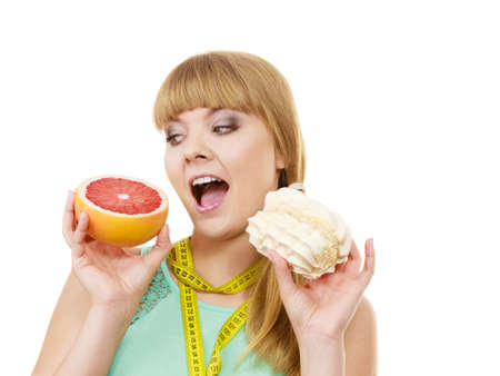 chose: Woman with measuring tape holds in hands cake and grapefruit choosing, deciding between sweet food or fresh fruit, make dietary choice. Weight loss diet dilemma concept. Isolated on white