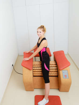 rid: Skincare, bodycare, wellness concept. Woman getting rid of thighs cellulite on big roll machine. Healthy massage treatment in spa