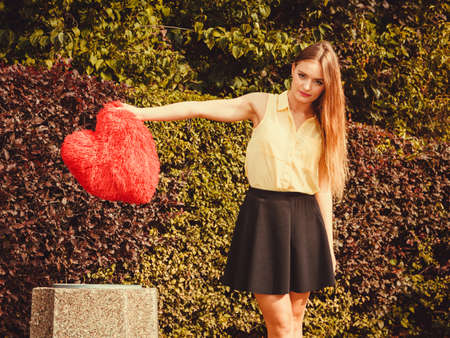 Love romance heartbreak sadness concept. Girl throwing heart into dustbin. Young lady holding plush love symbol over bin.