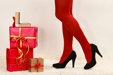 Fashionable woman long legs in red vivid color pantyhose black high heels shoes with many christmas gift boxes on white