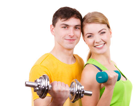 Couple fit woman and strong man exercising with dumbbells. Muscular guy and fitness blonde girl lifting weights. Bodybuilding. Stock Photo