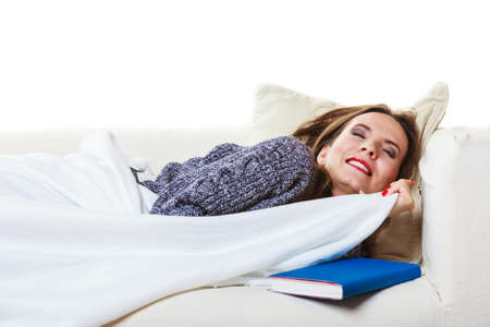tiredness: Health balance sleep deprivation concept. Sleeping woman on sofa. Girl lying on couch with book relaxed or taking power nap after lunch.
