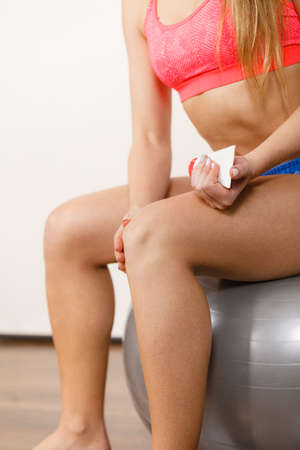 sprained joint: Woman fitness girl sitting on fit ball putting ointment cream on bad injured knee. Sport training gym and health care
