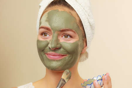 healt: Skin care. Woman applying with brush clay mud mask to her face. Girl taking care of oily complexion. Beauty treatment.