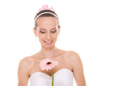 Attractive beautiful bride in white wedding dress holding pink gerbera daisy flower. Pretty young woman girl isolated on white background.