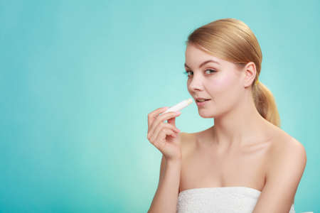 Female putting applying lip balm moisturizing balsam. Girl taking care of lips. Skincare. Stock Photo