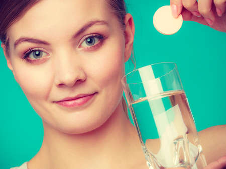 fizzy tablet: Vitamins, health, medicines. Woman holding glass with water and vitamin mineral supplement effervescent tablet. Studio shot on blue background