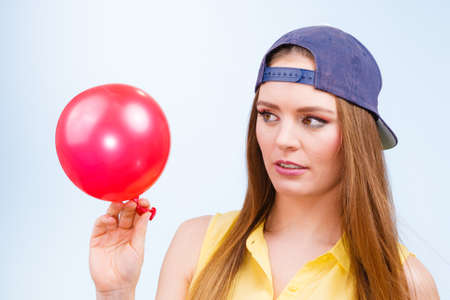 Teenage girl making funny silly faces. Young trendy woman in jeans cap holding red balloon.