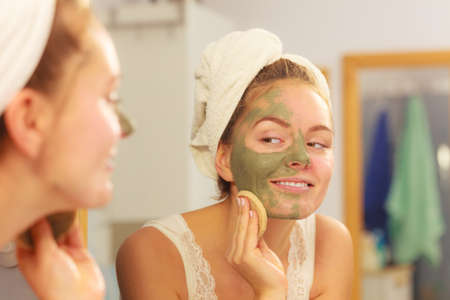Woman removing facial dried clay mud mask with sponge in bathroom in front of mirror. Skin care. Girl taking care of her complexion. Beauty spa treatment. Standard-Bild