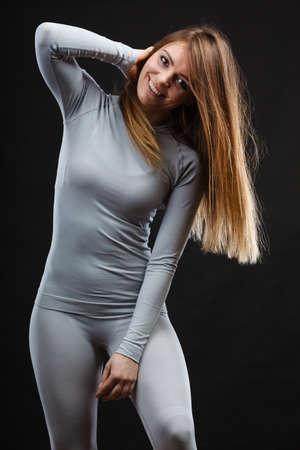 busty: Belleza seducive concepto de cuerpo en forma. Presentación atractiva de la chica. Joven dama sonriente presentando la moda ropa de la aptitud que muestra termoactivos.