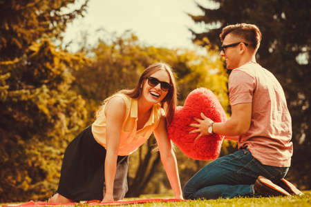 Love romance relationship dating leisure concept. Playful couple in park. Young girl boy spending time tossing heart outdoors.
