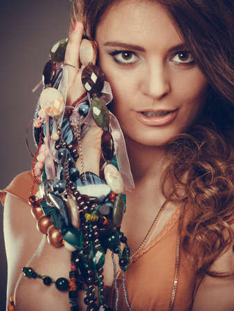 plentiful: Pretty young woman wearing bracelets and rings holding many plentiful of precious jewelry necklaces beads. Portrait of gorgeous fashion girl in studio on gray. Instagram filter.