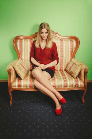 Attraktive hübsche junge Frau sitzt auf Vintage-Retro-Sofa Couch. Elegante moderne wunderschönen Mädchen, das kastanienbraune Hemd und Rock. Mode.