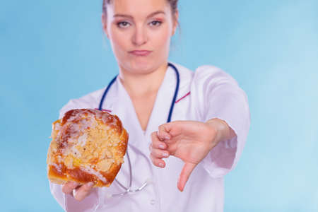 Dietitian nutritionist holding sweet roll bun showing thumb down gesture. Woman with fattening junk food. Bad unhealthy eating nutrition concept. Stock Photo