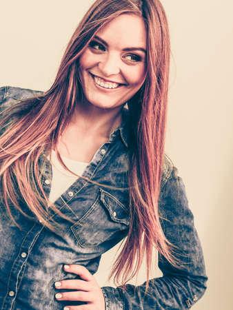 Smiling girl with arms on hips. Young woman in jeans jacket. Fashion beauty leisure concept.  Reklamní fotografie