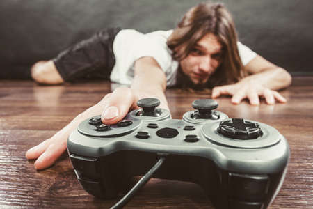 playstation: Addiction and dependency concept. Young man with pad joystick playing games. Male addicted to console playstation videogames.