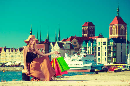 spending money: Spending money, buying things concept. Fashionable woman resting after big shopping, sitting with bags wearing glamorous outfit and big sun hat, Gdansk old town in background