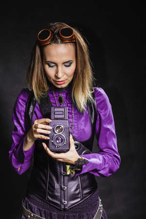 steampunk goggles: Photography and retro style. Young vintage attractive girl holds old aged camera. Steampunk photographer taking photo. Stock Photo