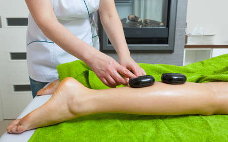 masseuse: Spa relaxation, healthy pleasure concept. Woman lying on stomach, female masseuse doing legs and feet massage with hot stones