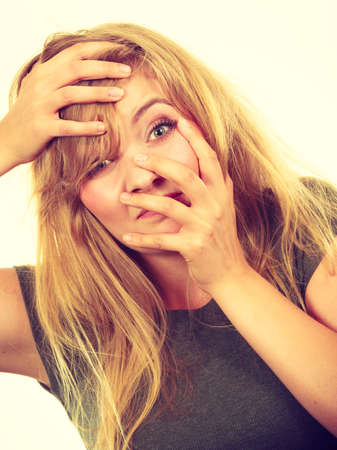 embarrassment: Emotions, embarrassment, awkwardness gestures concept. Ashamed blonde woman covering her face with hands. Studio shot on white background.