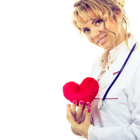 proffesional occupation: Periodic examinations. Cardiology concept. Female cardiologist holding red heart. Middle aged doctor with stethoscope and white medical apron uniform. Isolated on white.