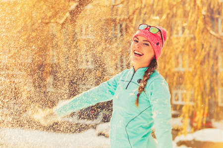 having fun in winter time: Girl having fun time with snow. Young woman playing in winter park. Health nature relax fashion fitness concept.