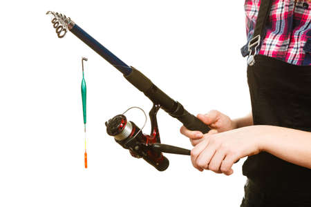 sportfishing: Fishing equipment concept. Woman holding fishing rod with green float. Isolated background. Stock Photo