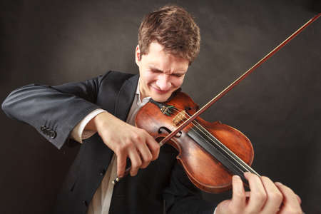 instrumentalist: Music passion, hobby concept. Man playing violin showing hard emotions and face expressions. Studio shot on dark background Stock Photo