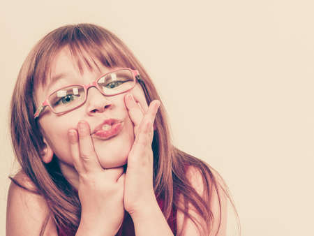 craze: Play and fun. Charming little girl making funny crazy face. Smiling lovely cute female child wearing glasses. Positive facial emotion.